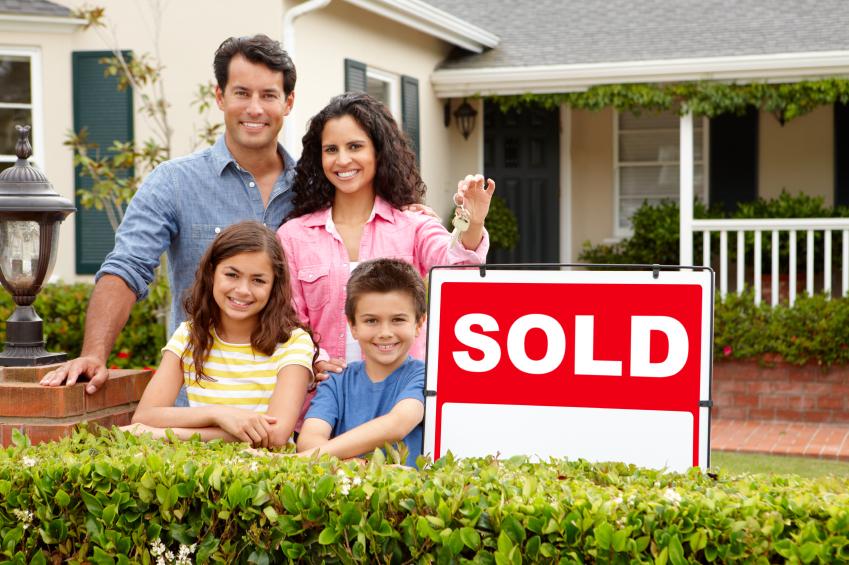 family outside home with sold sign