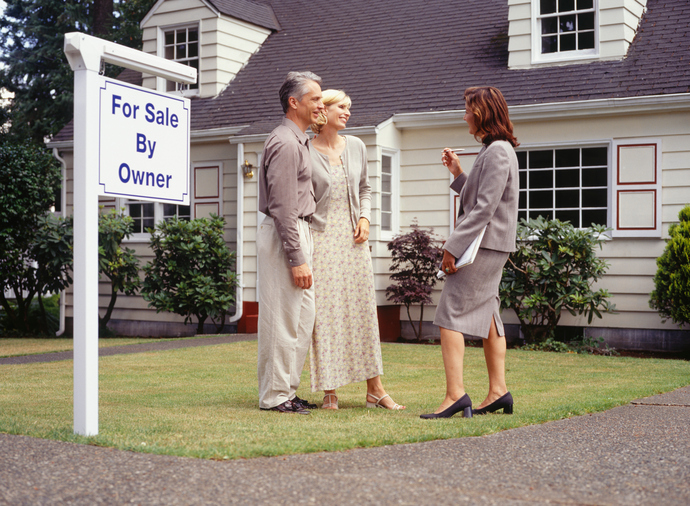 Couple talking to real estate agent on front lawn of house for sale