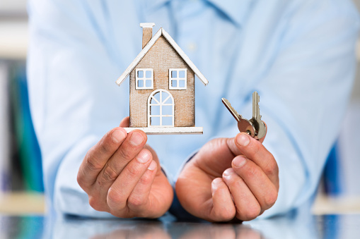 Male Hands holding Miniature House and House Key