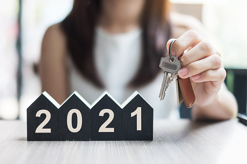 Young Businesswoman hands holding key and 2021 Happy New Year with house model on table office. New House, Financial, Property insurance, real estate, savings and New Year Resolution concepts